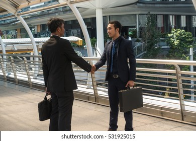 Two asian businessmen shake hands in the city.