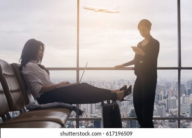 Two asian businesswoman sitting at airport and enjoying her laptop while waiting for her flight and using mobile phone with feeling happy and smiley face and town scene with airplane on background.