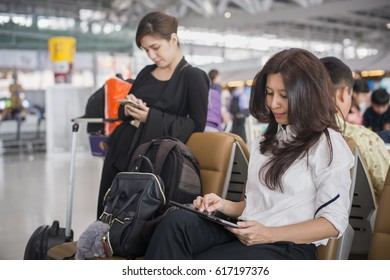 Two asian businesswoman sitting at airport and enjoying her tablet while waiting for her flight and background blurred asian woman using mobile phone with feeling happy at airport terminal.