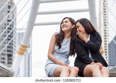 Two Asian businesswomen gossip joke story at outdoors city after finished working. Business women coworker and friendship concept. Beautiful business people talking secret scandal topic in office life