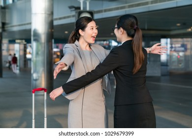 Two Asian businesswomen met each other so happy. They are going to give each other a big hug.