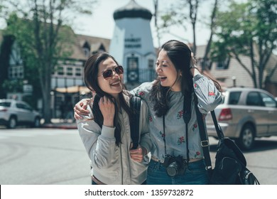 two asian cheerful laughing photographer travel carrying bag smiling outdoor on street walking on sunny day. happy girls hugging together shopping in solvang santa barbara usa lifestyle best friends.