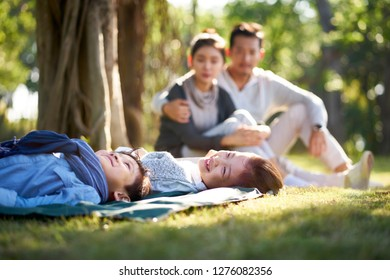 two asian children little boy and girl having fun lying on grass with parents sitting watching in background.