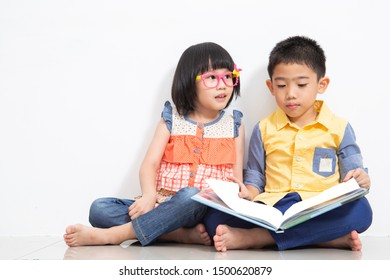 Two Asian children read a book in the guest room.
