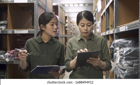 Two asian chinese girl workers in warehouse use digital tablet with document paper together. female staff colleagues walking in rows of shelves in stockhouse having discussion. women team partners