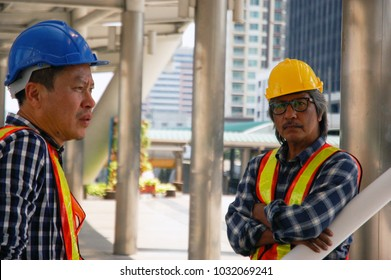 Two Asian construction workers discuss about plan for renovate building project, have some peoblem about floor concret. Serious faces, talking to find new way to work with engineer team, strong team.