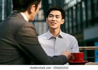 two asian corporate businesspeople discussing business at a outdoor coffee shop