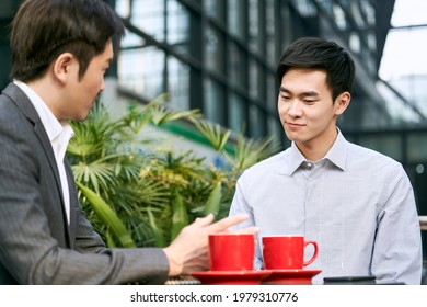 two asian corporate businesspeople discussing business at a outdoor coffee shop - Shutterstock ID 1979310776