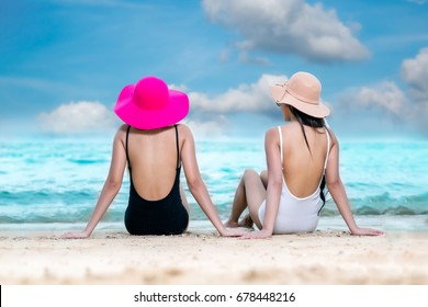two asian cute girl sitting relaxed in ocean paradise beach. view from behind.