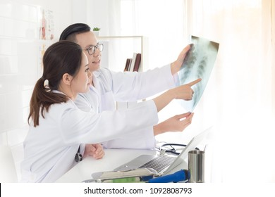 two Asian doctor looking patient film and discussion about patient symptom, respiratory treatment, treatment consultation, chest x-ray