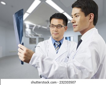 two asian doctors looking at x-ray film.