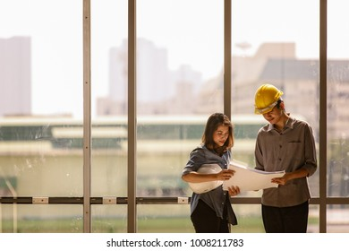 Two Asian engineer, male with yellow safety helmet and woman with white one standing and talking near high curtain wall glass frame in construction site. Both looking at blueprint paper.