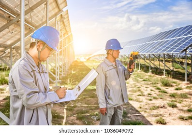 Two Asian engineers are testing photovoltaic panels