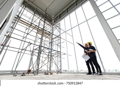 Two asian engineers working in construction site, man in white safety helmet is pointing to scaffold and female in yellow helmet loot at there.