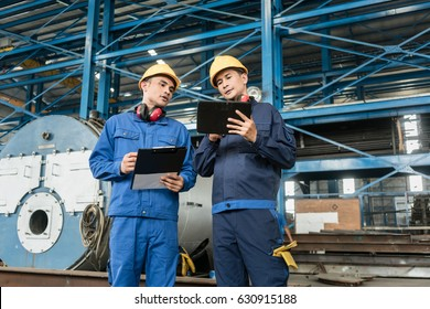 Two Asian experts checking information during quality control in the interior of a factory