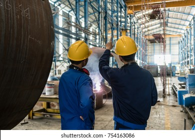 Two Asian experts talking while supervising the fabrication of industrial boilers indoors