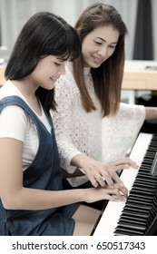 Two Asian family, mother and daughter learn to play piano together in home, mom in blur background, process in vintage style