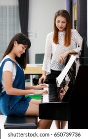 Two Asian family, mother and daughter learn to play piano together in home, mom in blur background