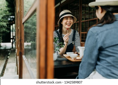 two asian female best friends gathering together on tea ceremony party eating japanese sweets cakes enjoyment happiness. beautiful girls traveler in tokyo lifestyle. summer zen garden teien view.