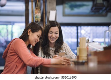 two asian female friends chatting in a traditional Japanese restaurant in Kyoto