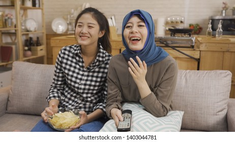 two asian female friends eating potato chips and watching tv show. multi ethnic people young girls chinese and muslim sitting on couch laughing cheerfully watch comedy on television at home kitchen