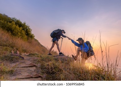 Two asian female hikers climbing up silhouette mountain cliff . Helping ,helps and team work concept.