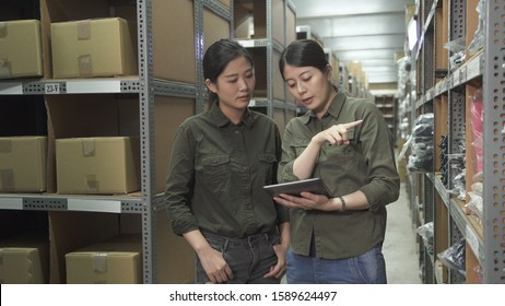 Two asian female staff inspecting products in factory warehouse. lady colleagues in uniform working together in stockhouse and using mobile touch pad point on shelves teaching new in employee.