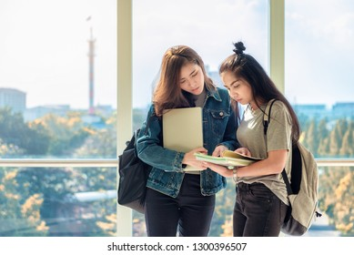 Two Asian female students discussing and pointing finger to notes in book for finding the correct answer for their question preparing for university examination. Life of studying and friendship.