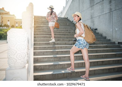Two Asian friends climbing stairs in Taipei national palace museum, a famous popular historic traditional Chinese building.