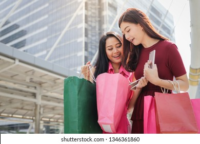 Two asian friends Showing many stuffs from the bags after shopping in the city
