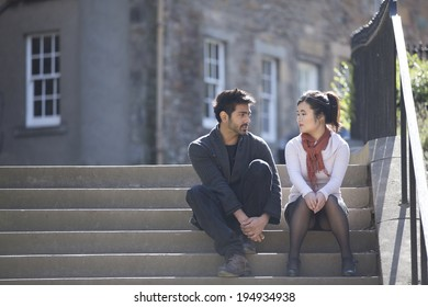 Two Asian friends sitting outdoors relaxing. Young urban couple 'hanging out' in the city
