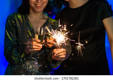 two Asian girls hold sparklers and champagne for the new year. holiday of Christmas