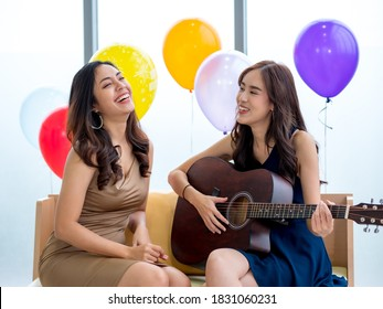 Two Asian girls play guitar and sing at Christmas party