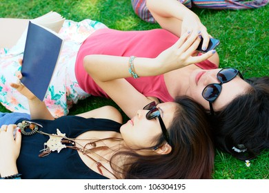 two asian girls relaxing on a grass