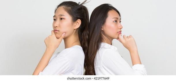 Two Asian girls thinking