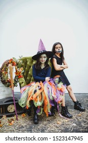 Two Asian girls wearing costume and boots. Children with face painting. Witch and skeleton kids. Rustic furniture in the outdoors. Antique clock. Black dress. Kids activity and fall photo shoot.