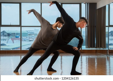 Two Asian guys dancing beautiful contemporary dance simultaneously near huge window in studio