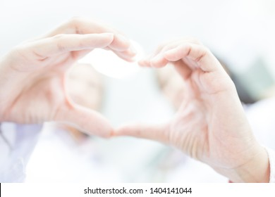 two Asian healthcare worker show heart sigh with hands , unity and teamwork, on white background