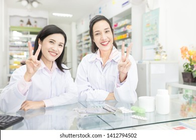 two Asian healthcare worker show v sigh with hands , unity and teamwork, on white background, happiness organization, asian pharmacist in drugstore