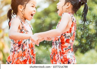 Two asian little child girls holding hand jumping and playing water together in summer time with fun and happiness