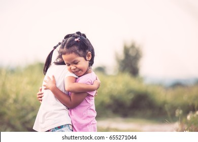 Two asian little child girls hugging each other with love in the garden in vintage color tone