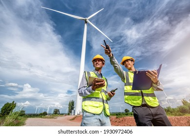 two asian male engineers working on site with wind turbine propeller and clear blue sky on the background. Alternative energy, environmental friendly for the future. clean energy innovation.