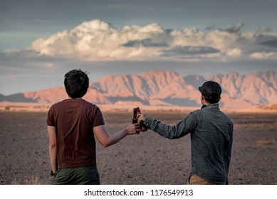 Two Asian man traveler clinking bootle drinking beer while looking at scenery during the sunset in Namibia, Africa. Friendship, travel and celebration concepts