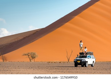 Two Asian man traveler and photographer standing and sitting on camper car near orange sand dune. Travel desert concept