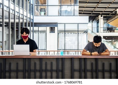 Two asian man wear a face mask for protecting the virus while working in office with the laptop in casual and keep social distancing. New normal concept.