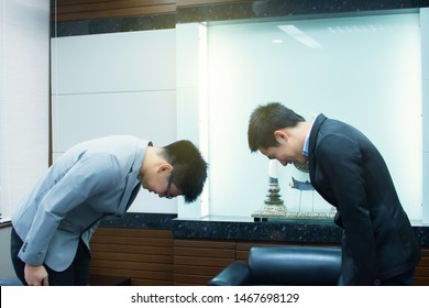 Two asian men bowing for business manner after dealing agreement