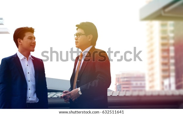 Two asian men are talking business with building background