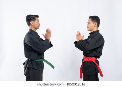 two Asian men wearing pencak silat uniforms stand opposite each other with mutual respect on the isolated background