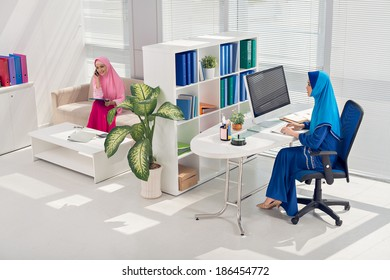 Two Asian Muslim businesswomen doing some work in the office
