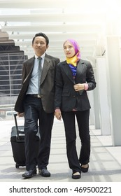 Two Asian Muslim executive wearing suit outdoor talking